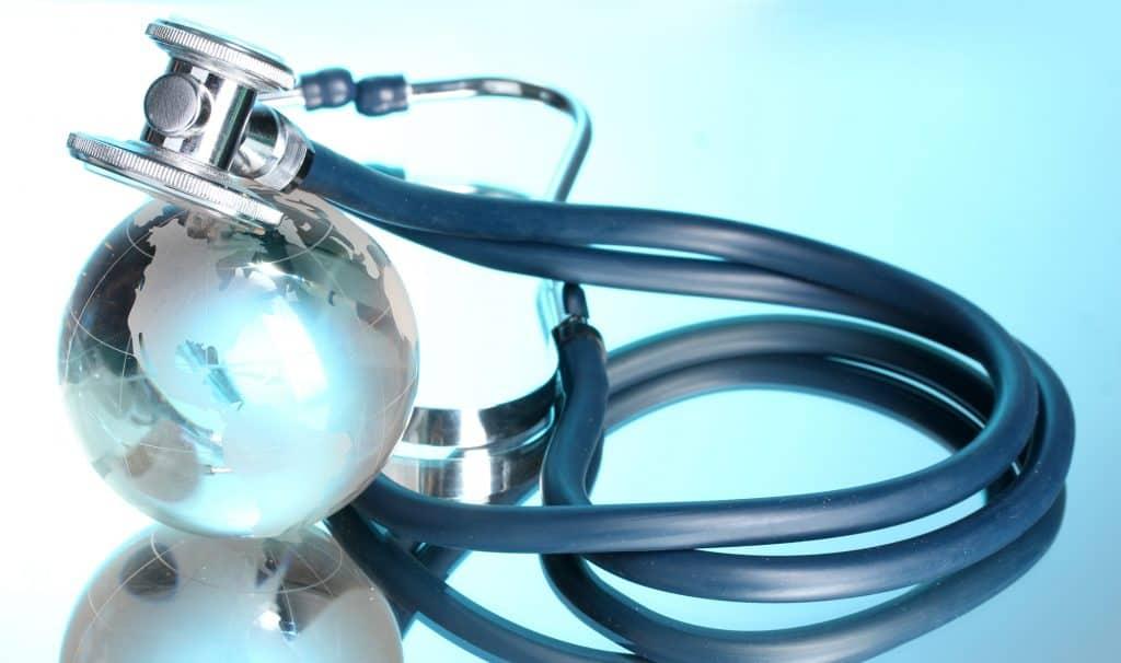 Globe and stethoscope on blue